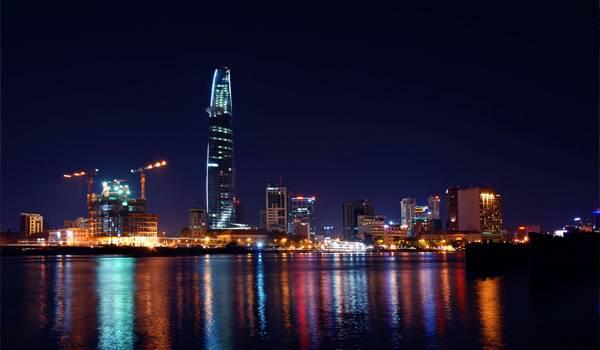 Здание Bitexco отражается в ночной реке Сайгон
